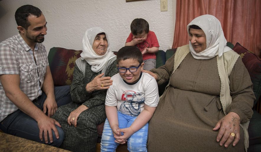 In a Thursday May 31, 2018 photo, Ali Turki Ali, far left, laughs as his step-mother Faiza, second from left, and his mother, Amina, right, watch their grandsons be silly at their new home in Eugene, Ore. The women arrived recently from Turkey where they had been staying since fleeing the war in Syria in 2014. (Andy Nelson/The Register-Guard via AP)
