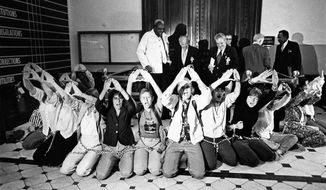 FILE - In this June 3, 1982 file photo, a group of feminists chained themselves together outside the Illinois Senate chambers in Springfield, Ill., to show support for the ratification of the ERA The women chanted and held their hands in the shape of a womb to symbolize womanhood. Illinois for decades remained the only industrial northern state not to ratify the federal Equal Rights Amendment. But decades after the Congressional deadline the state finally approved the resolution. (AP Photo/File)