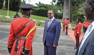Ethiopia's new Prime Minister Abiy Ahmed, 42, who was installed in April, inspects the honor guard as he arrives to meet for bilateral talks with Uganda's President Yoweri Museveni at State House in Entebbe, Uganda Friday, June 8, 2018. Sweeping changes that seemed unthinkable just weeks ago have been announced almost daily since Ahmed, Africa's youngest head of government, took office and vowed to bring months of deadly protests to an end. (AP Photo/Ronald Kabuubi)