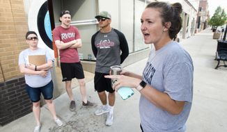 Morningside student Hallie Misiaszek talks about the scandalous past of Sioux City, Iowa, during a practice of the tour on Pearl Street in in Sioux City Thursday, May 24, 2018. (Justin Wan/Sioux City Journal via AP)