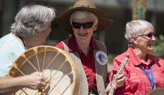 In this May 7, 2018, photo, Terry Covington, from left, Kitty Ash and Suzanne Philbrook, who are part of the Traveling Day Society, a ministry of All Saints Episcopal Church that performs native music at funerals, hospices and hospitals, perform at the Legacy Salmon Creek Medical Center's healing garden in Vancouver, Wash. (Alisha Jucevic/The Columbian via AP)