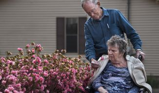 Harold Johnson presents Sandra with a flower from the Azalea bushes lining their home on Wednesday, April 11, 2018, in Jackson, Tenn..   Sandra was diagnosed with severe dementia and Harold kept her at home until just over a year ago, when it progressed to the point where he couldn't take care of her alone. Sandra is to the point where she cannot communicate or do anything without assistance. Sticking true to vows, Johnson hasn't given up on his first and only serious love.   (Morgan Timms/The Jackson Sun via AP)