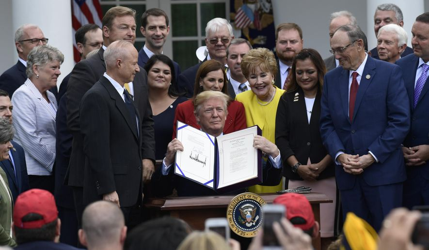 "In this June 6, 2018, photo, President Donald Trump holds up the ""VA Mission Act of 2018"" that he signed during a ceremony in the Rose Garden of the White House in Washington. (AP Photo/Susan Walsh)"