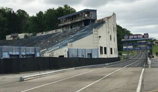 In this June 6, 2018 photo, the abandoned Akron Rubber Bowl stadium is pictured with the adjacent Derby Downs soap box derby track in Akron, Ohio.  Part of the historic stadium is being torn down starting next week because it's a public health hazard. (AP Photo/Mitch Stacy)