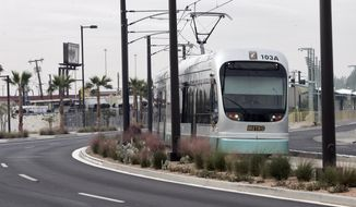 FILE -- A Metro light rail train runs along Washington St. Monday, Dec 22, 2008 in Phoenix. A planned 6-mile spur into south Phoenix to expand the metro area's light rail system is already approved with construction expected to begin in 2019, but critics are hoping to persuade the City Council to reverse course and derail the project.(AP Photo/Matt York)