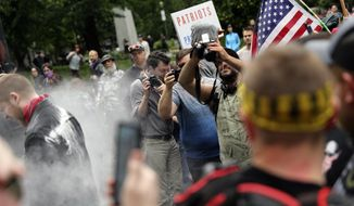 In this June 3, 2018, file photo, photographers capture dueling demonstrations between antifacists known as antifa and a right-wing group called Patriot Prayer in downtown Portland, Ore. (Mark Graves/The Oregonian via AP, file)
