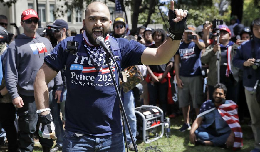 """In this April 27, 2017, file photo, right wing group Patriot Prayer leader Joey Gibson speaks during a rally in support of free speech in Berkeley, Calif. The conflict between Patriot Prayer and the so-called """"antifa"""" has dominated the landscape at marches and rallies in Portland, Ore., in recent months, creating turmoil and soul-searching in the city, a liberal bastion that also hides a dark and lesser-known history of racism dating back decades. (AP Photo/Marcio Jose Sanchez, file)"""