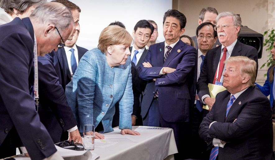 German Chancellor Angela Merkel (center) speaks with President Trump (seated at right) during the G-7 Leaders Summit in La Malbaie, Quebec, Canada, on Saturday. (Associated Press)