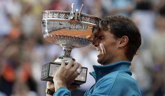 Spain's Rafael Nadal holds the trophy as he celebrates winning the men's final match of the French Open tennis tournament against Austria's Dominic Thiem in three sets 6-4, 6-3, 6-2, at the Roland Garros stadium in Paris, France, Sunday, June 10, 2018. (AP Photo/Alessandra Tarantino)
