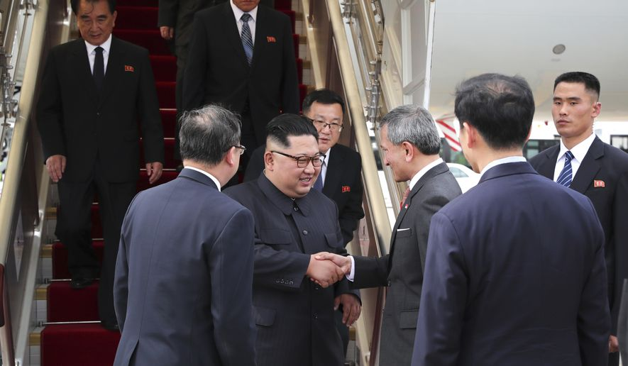 In this photo released by the Ministry of Communications and Information of Singapore, North Korean leader Kim Jong Un, center left, is greeted by Singapore Minister for Foreign Affairs Dr. Vivian Balakrishnan at the Changi International Airport, Sunday, June 10, 2018, in Singapore, ahead of a summit with U.S. President Donald Trump. (Ministry of Communications and Information Singapore via AP)