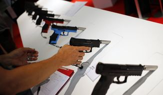 A man checks handguns displayed at the Eurosatory defense and security trade show in Villepinte, outside Paris, Sunday, June 10, 2018. (AP Photo/Francois Mori) ** FILE **