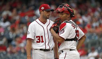 Washington Nationals starting pitcher Max Scherzer, left, and catcher Pedro Severino, right,  talk on the mound during the fourth inning of a baseball game against the San Francisco Giants at Nationals Park, Sunday, June 10, 2018, in Washington. (AP Photo/Alex Brandon)