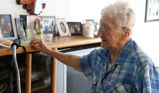 In this Thursday May 31, 2018 photo, Pauline Phillips recalls family memories at her home in Roseburg, Ore. Pauline Phillips leads a busy life. She still drives, does water aerobics every morning at the YMCA, leads Rosary at the Catholic Church and serves dinner at the Elks lodge, defying the fact that she is 98 years old. She was born on April 21, 1920 and has outlived two husbands.  (Michael Sullivan/The News-Review via AP)
