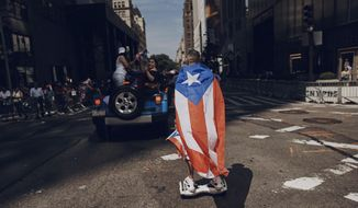 FILE - In this June 11, 2017 file photo, a man rolls on a hover-board along Fifth Avenue during the National Puerto Rican Day Parade in New York.  Amid all the fun and celebration planned for this years parade on Sunday, June 10, 2018, organizers and participants want to keep a spotlight on something serious. They want people to remember that months after Hurricane Maria roared through and as the next hurricane season arrives, Puerto Rico is still struggling. (AP Photo/Andres Kudacki)