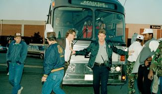 A Fairfax County police officer holds back Washington Redskin players R.C. Thielemann, glasses, left, and Darryl Grant, right, as a busload of newly recruited players arrives September 23, 1987 at the Redskins Park practice facility in Chantilly, Virginia. The Football Players' Association voted to strike on Sept. 22, 1987.  The National Football League Players Association's stike is against the owners and the National Football League.     (AP Photo/Dennis Cook)