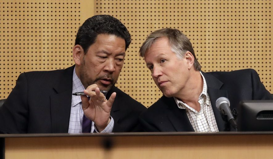 Seattle City Council City President Bruce Harrell, left, speaks with council member Mike O'Brien before the council voted to approve a tax on large businesses such as Amazon and Starbucks to fight homelessness, Monday, May 14, 2018, in Seattle. The council on Monday unanimously backed a compromise tax plan that will charge large businesses about $275 per full-time worker a year. It's lower than the $500-per-worker tax initially proposed. The tax would begin in 2019 and raise about $48 million a year to pay for affordable housing and homeless services. (AP Photo/Elaine Thompson)