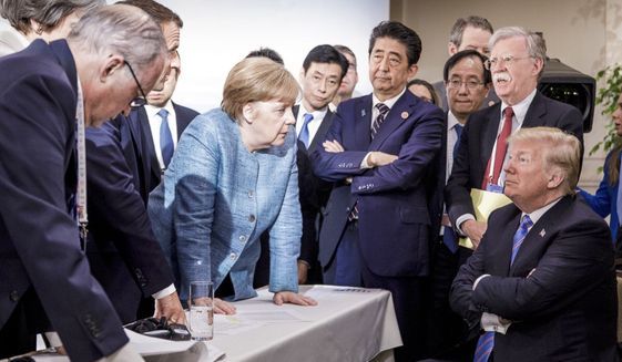 In this photo made available by the German Federal Government, German Chancellor Angela Merkel, center, speaks with U.S. President Donald Trump, seated at right, during the G7 Leaders Summit in La Malbaie, Quebec, Canada, on Saturday, June 9, 2018. (Jesco Denzel/German Federal Government via AP)