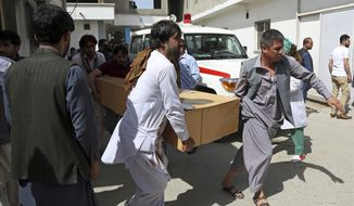 Relatives carry the coffin of a victim after a deadly suicide attack, in Kabul, Afghanistan, Monday, June 11, 2018. Afghan officials said a suicide bomber on foot struck the Rural Rehabilitation and Development Ministry as employees were leaving work in the capital, killing at least 12 people and wounding over 30 days before the start of a holiday cease-fire with the Taliban. (AP Photo/Rahmat Gul)