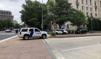 Authorities remain at the Justice Department on Monday evening after an apparent hoax call reporting an active shooter. (Jeff Mordock/The Washington Times)