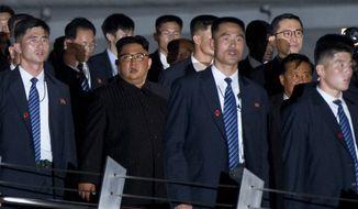 North Korean leader Kim Jong Un, center, walks in Marina Bay, Singapore Monday, June 11, 2018 ahead of the summit with U.S. President Donald Trump. (AP Photo/Gemunu Amarasinghe)