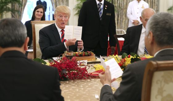 In this photo released by the Ministry of Communications and Information of Singapore, U.S. President Donald Trump gets an early birthday celebration during lunch with Singapore's Prime Minister Lee Hsien Loong in Singapore, Monday, June 11, 2018. Trump turns 72 on Thursday. (Ministry of Communications and Information Singapore via AP)