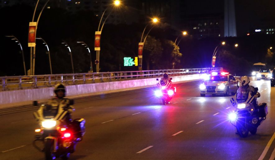 North Korean leader Kim Jong Un's entourage drives through downtown Singapore on Monday, June 11, 2018. (AP Photo/Wong Maye-E)
