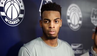 NBA draft prospect Troy Brown Jr., right, from Oregon, listens to a question from the media after an NBA pre-draft basketball workout Monday, June 11, 2018, in Washington. (AP Photo/Alex Brandon) ** FILE **