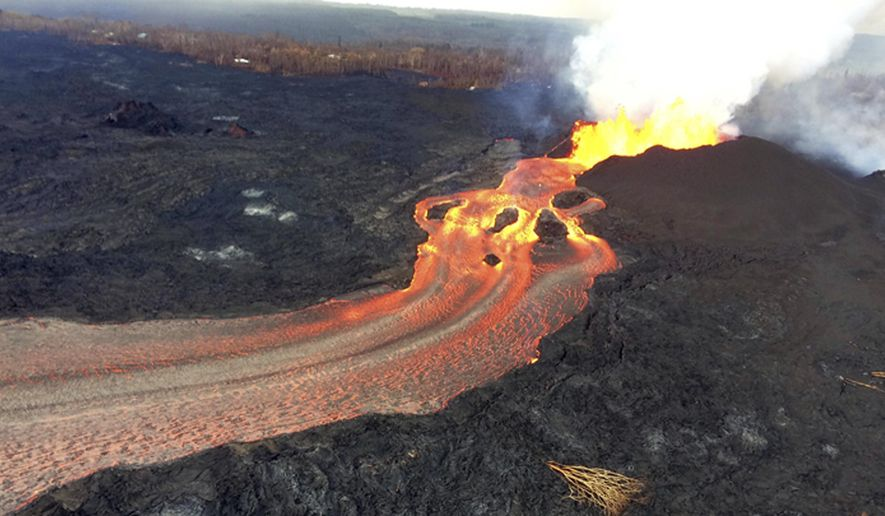 In this Sunday, June 10, 2018 photo from the U.S. Geological Survey, fissure 8 below Kilauea Volcano continues to erupt vigorously with lava streaming through a channel that reaches the ocean at Kapoho Bay on the island of Hawaii . The width of the active part of the lava channel varies along its length, but ranges from about 100 to 300 meters (yards) wide. A clear view of the cinder-and-spatter cone that's building around the vent from ongoing lava fountains can be seen here. (U.S. Geological Survey via AP)