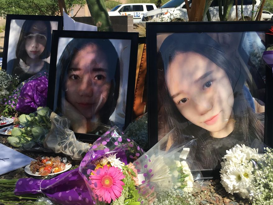 Yue Jiang is shown in large photographs at a memorial over two years after her death in Tempe, Ariz. on Monday, June 11, 2018.  The family of 19-year-old Yeu Jiang traveled from China to Arizona this week to plead with a judge to reject a deal that prosecutors made with suspect Holly Davis that reduces her charges. (AP Photo/Astrid Galvan)