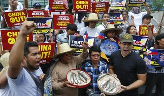 Protesters shout slogans while displaying small catch during a rally at the Chinese Consulate in the financial district of Makati city to protest alleged continued seizure of catches of Filipino fishermen at a disputed shoal in the South China Sea despite a protest by the Philippines following an earlier incident Monday, June, 11, 2018 east of Manila, Philippines. The Philippines expressed concern to China in a meeting in Manila in February after receiving a report of Chinese coast guard personnel boarding a Filipino fishing boat at Scarborough Shoal and taking some of its catch, officials said. (AP Photo/Bullit Marquez)