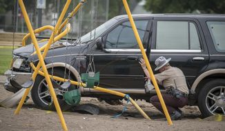 Minnesota State Patrol investigates the scene where a motorist being pursued by the State Patrol veered into a Minneapolis school playground Monday, June 11, 2018. At least two young children suffered life-threatening injuries after police say a motorist being pursued by the State Patrol veered into a Minneapolis park and struck them. The State Patrol says the driver ran from the crash scene and was arrested. (Elizabeth Flores/Star Tribune via AP)