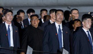 North Korean leader Kim Jong-un, center, walks in Marina Bay, Singapore Monday, June 11, 2018, ahead of the summit with U.S. President Donald Trump. (AP Photo/Gemunu Amarasinghe)