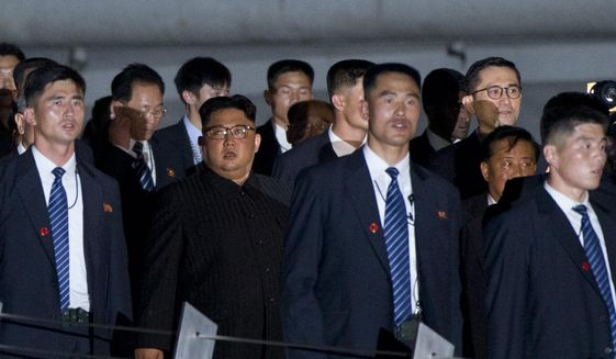 North Korean leader Kim Jong-un, center, walks in Marina Bay, Singapore Monday, June 11, 2018, ahead of the summit with U.S. President Donald Trump. (AP Photo/Gemunu Amarasinghe)