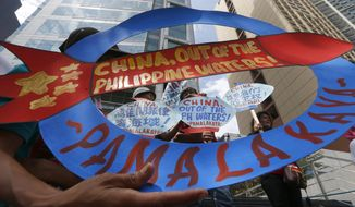 FILE - In this May 18, 2018, file photo, protesters display placards during a rally at the Chinese Consulate to protest China's deployment of missiles on the Philippine-claimed reefs in South China Sea in the financial district of Makati city east of Manila, Philippines. Filipino officials say China's coast guard has continued to seize the catches of Filipino fishermen at a disputed shoal. (AP Photo/Bullit Marquez, File)