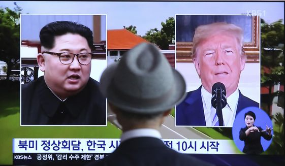 """A man watches a TV screen showing file footage of U.S. President Donald Trump, right, and North Korean leader Kim Jong-un during a news program at the Seoul Railway Station in Seoul, South Korea, Monday, June 11, 2018.  Final preparations are underway in Singapore for Tuesday's historic summit between President Trump and North Korean leader Kim, including a plan for the leaders to kick things off by meeting with only their translators present, a U.S. official said.  The signs read: """" Summit between the United States and North Korea."""" (AP Photo/Ahn Young-joon)"""
