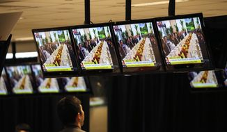 Members of the press watch a live telecast of U.S. President Donald Trump's bilateral meeting with Singapore's Prime Minister Lee Hsien Loong on Monday, June 11, 2018, in Singapore, at the international media center. In their final hours of calm, President Donald Trump and North Korea's Kim Jong Un huddled with advisers in luxury Singapore hotels less than half a mile apart, readying for a nuclear summit that could define the fate of millions, and their own political futures. (AP Photo/Wong Maye-E)