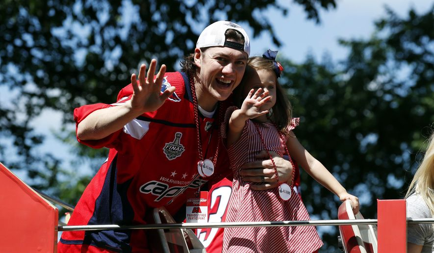 Washington Capitals right wing T.J. Oshie waves while holding his daughter Lyla Oshie during a Stanley Cup NHL hockey victory parade, Tuesday, June 12, 2018, in Washington. (AP Photo/Alex Brandon, Pool) ** FILE **
