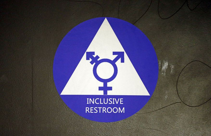 In this May 17, 2016, file photo, a new sticker designates a gender neutral bathroom at Nathan Hale high school in Seattle. (AP Photo/Elaine Thompson, File)