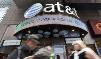 FILE - In this Oct. 21, 2014, file photo, people pass an AT&T store in New York's Times Square. AT&T reports financial results Tuesday, Oct. 25, 2016. (AP Photo/Richard Drew, File)