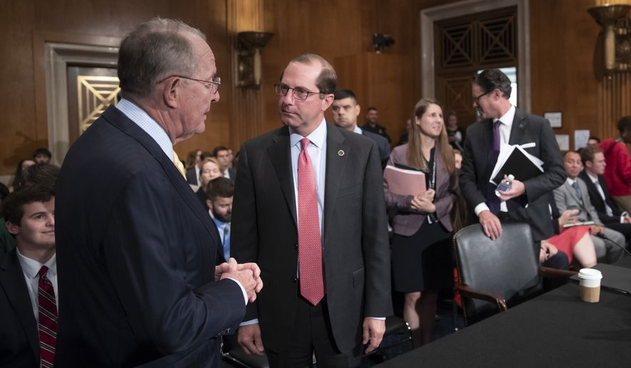 Sen. Lamar Alexander, R-Tenn., left, chairman of the Senate Health, Education, Labor, and Pensions Committee, greets Secretary of Health and Human Services Alex Azar the witness at a hearing on prescription drug prices, on Capitol Hill in Washington, Tuesday, June 12, 2018. (AP Photo/J. Scott Applewhite)