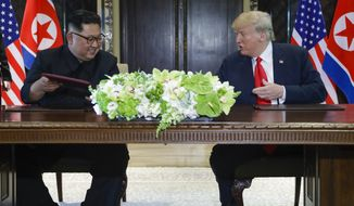 North Korea leader Kim Jong Un and U.S. President Donald Trump exchanged signed documents at the Capella resort on Sentosa Island Tuesday, June 12, 2018 in Singapore. (AP Photo/Evan Vucci)