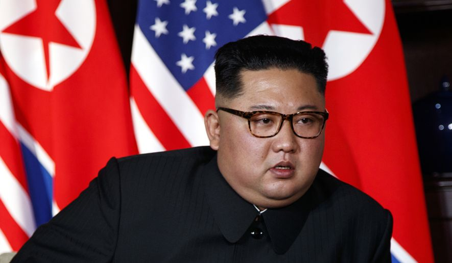 North Korean leader Kim Jong-un listens to U.S. President Donald Trump during a meeting on Sentosa Island in Singapore Tuesday, June 12, 2018. Kim showed up in an old communist uniform without a lapel pin with the images of his late father and grandfather who ruled successively before his inauguration in late 2011. (AP Photo/Evan Vucci)