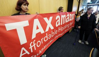 """Demonstrators opposing the repeal of a tax on large companies such as Amazon and Starbucks that was intended to combat a growing homelessness crisis hold a sign that reads """"Tax Amazon"""" as they wait for the start of a Seattle City Council meeting, Tuesday, June 12, 2018, at City Hall in Seattle. Members of the Council were expected to vote Tuesday on whether or not to repeal the tax. (AP Photo/Ted S. Warren)"""