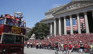 Washington Capitals left wing Alex Ovechkin (8), from Russia, holds up the Stanley Cup as they pass the crowd on the steps of The National Archives during a victory parade, Tuesday, June 12, 2018, in Washington. (AP Photo/Alex Brandon, Pool)
