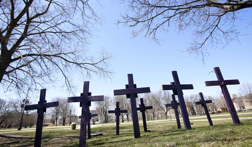 FILE - In this Thursday, April 19, 2018 file photo, crosses representing victims of gun violence stand outside Collins Academy High School in Chicago's North Lawndale neighborhood. With frustration mounting over lawmakers' inaction on gun control, the American Medical Association on Tuesday, June 12, 2018, pressed for a ban on assault weapons and came out against arming teachers as way to fight what it calls a public health crisis. (AP Photo/Martha Irvine)