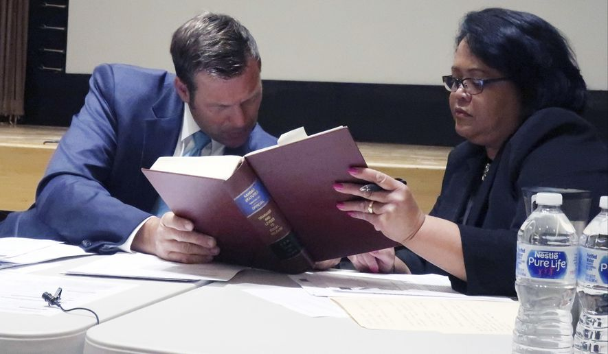 Kansas Secretary of State Kris Kobach, left, confers with Deputy Attorney General Athena Andaya, right, over state election laws during a meeting of the State Objections Board, Monday, June 11, 2018, in Topeka, Kan. The board has decided to list two candidates with the same first and last names in a Republican congressional primary as Rep. Ron Estes and Ron M. Estes. (AP Photo/John Hanna)