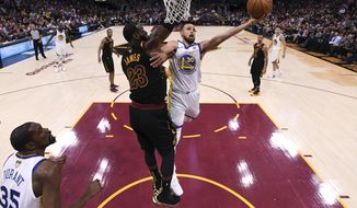 Golden State Warriors guard Stephen Curry (30 shoots around Cleveland Cavaliers forward LeBron James (23) in Game 4 of basketball's NBA Finals on Friday, June 8, 2018, in Cleveland. The Warriors defeated the Cavaliers 108-85 to sweep the series. (Gregory Shamus/Pool Photo via AP)