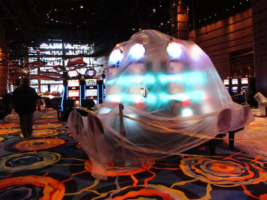 This June 12, 2018 photo shows a bank of illuminated slot machines under plastic wrap inside the Ocean Resort Casino as the former Revel property prepares to reopen under a new owner and a new brand on June 28. (AP Photo/Wayne Parry)