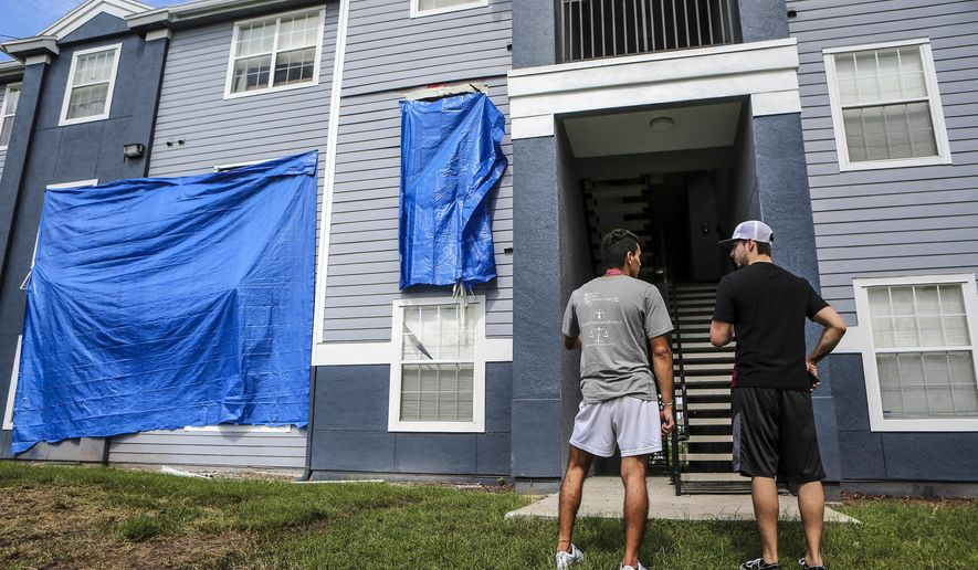 Residents at Westbrook Apartments get a first look at their building where a gunman held four children hostage before taking their life and his own, Tuesday, June 12, 2018, in Orlando, Fla. The children were discovered dead at the west Orlando apartment complex late Monday, nearly 24 hours after a standoff that began when an Orlando police officer was shot responding to a domestic violence call. (Jacob Langston/Orlando Sentinel via AP)