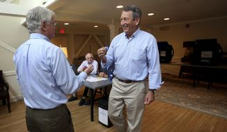 Poll volunteer Tom Spain hands out stickers to former Gov, Mark Sanford after he cast his own ballot at Alhambra Hall polling station Tuesday, June 12, 2018, in Mt. Pleasant, S.C. (Grace Beahm Alford/The Post And Courier via AP)